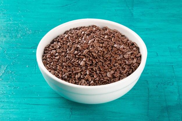 Cioccolato granulato in ciotola bianca con superficie blu.