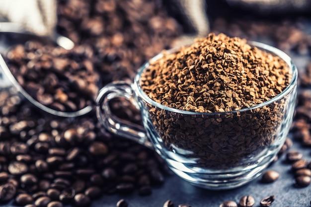 Granuli di caffè istantaneo in tazza di vetro e chicchi di caffè.
