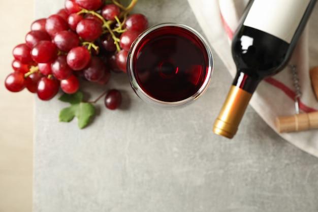 Uva, bottiglia e bicchiere con vino su grigio