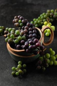Grappoli d'uva in tazze di ceramica su sfondo grigio