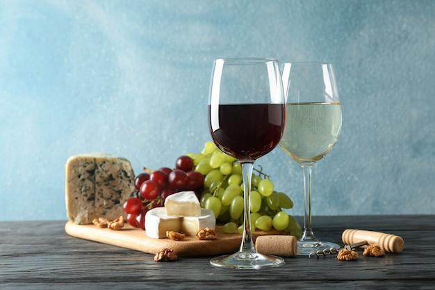 Uva, formaggio, cavatappi, bicchieri con vino