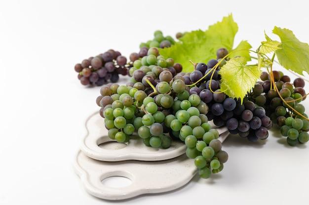 Grappoli d'uva verde e blu su sfondo bianco