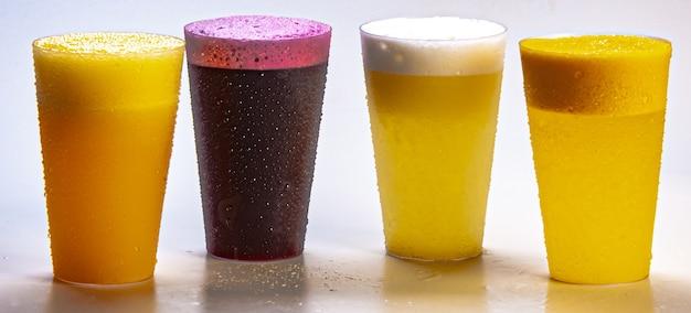 Succo d'uva, succo d'arancia, succo d'ananas e succo di frutto della passione, freschi e ghiacciati - bevande salutari su sfondo bianco