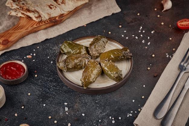 Foglie di vite con carne, cucina georgiana, sfondo scuro con texture