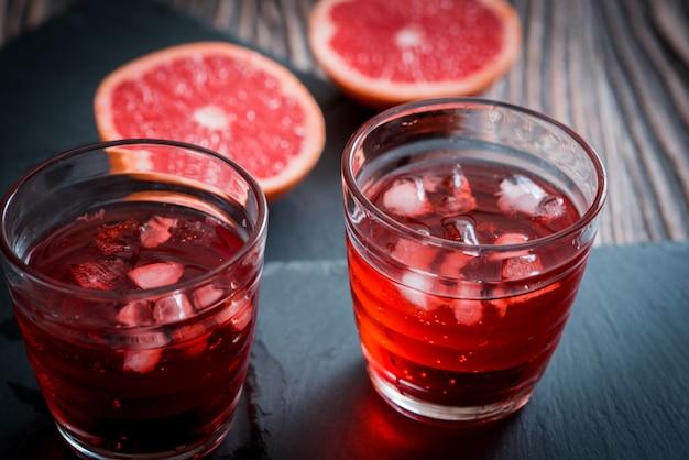 Bicchiere di limonata al pompelmo con cubetti di ghiaccio e goccioline.