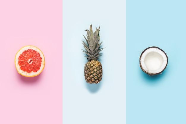 Pompelmo, ananas e cocco su diversi sfondi colorati.