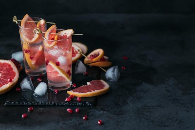 Cocktail o mocktail di pompelmo e melograno, rinfrescante bevanda estiva con ghiaccio tritato e acqua frizzante