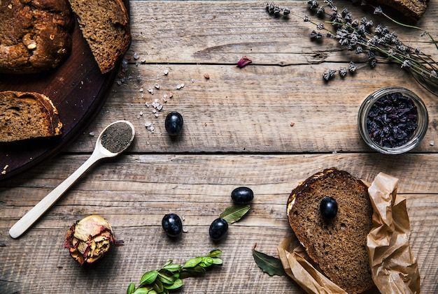 Uva, grano, pane nella tavola di legno. rose essiccate. fiori. frutta, cereali, cibo