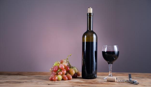 Bottiglia di vino dell'uva e vetro con l'apri sul tavolo Foto Premium