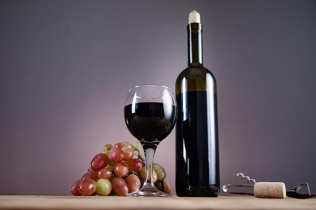 Bottiglia di vino dell'uva e vetro con l'apri sul tavolo