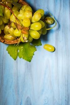 Uva con foglie sullo sfondo di legno