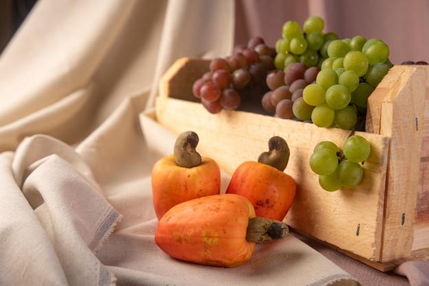 Uva in una scatola di legno e anacardi con tessuti in background, bassa profondità di campo