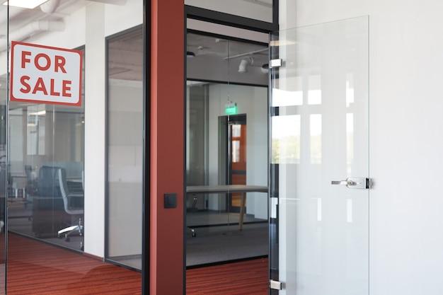 Immagine di sfondo grafico dell'interiore dell'ufficio vuoto con il segno rosso per la vendita sulla porta di vetro, spazio della copia