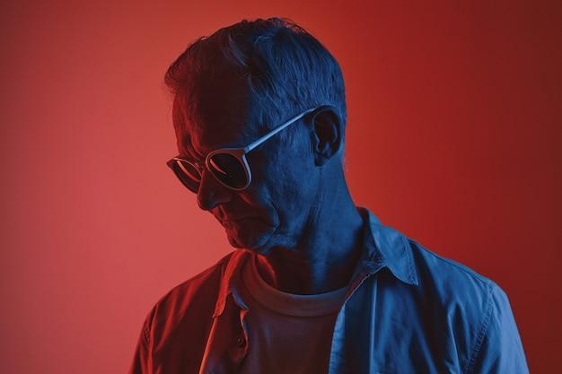 Ritratto grafico colorato di un uomo anziano che indossa occhiali da sole in rosso e blu, copia spazio