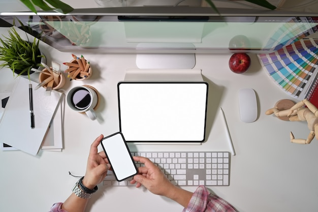 Progettista grafico creativo che utilizza il telefono cellulare e lavora con la tavoletta grafica con display digitale