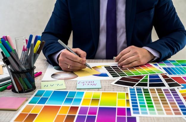 Graphic designer che sceglie un colore da un campionatore in ufficio. campioni di colore. mani dell'uomo che scelgono un colore da un campionatore