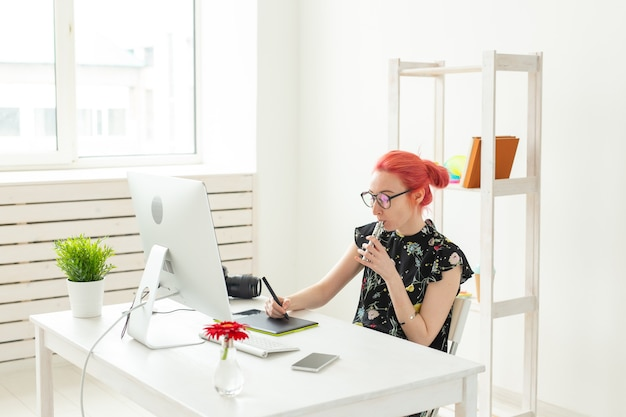 Concetto di graphic designer - designer grafico femminile che lavora al computer mentre utilizza la tavoletta grafica alla scrivania in ufficio e fuma uno svapo.