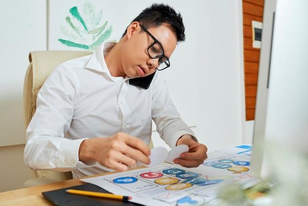 Graphic designer che parla al telefono con un cliente o un collega quando lavora al layout dell'app mobile...