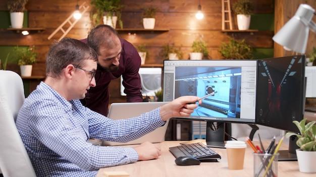 Graphic designer che lavora nel settore dei giochi che mostra il nuovo design del gioco virtuale al suo collega