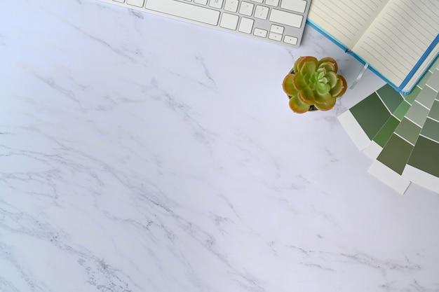 Area di lavoro del progettista grafico con tastiera, campione di colore e taccuino su fondo di marmo.