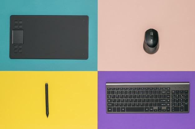 Tavoletta grafica, tastiera e mouse wireless su sfondo a quattro colori. gli strumenti di un designer.