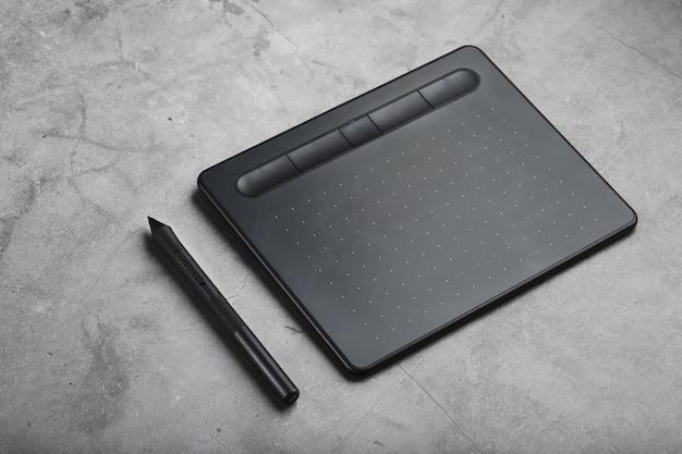 Tavoletta grafica con una penna su uno sfondo grigio, il lavoro di un designer, artista e fotografo. la vista dall'alto