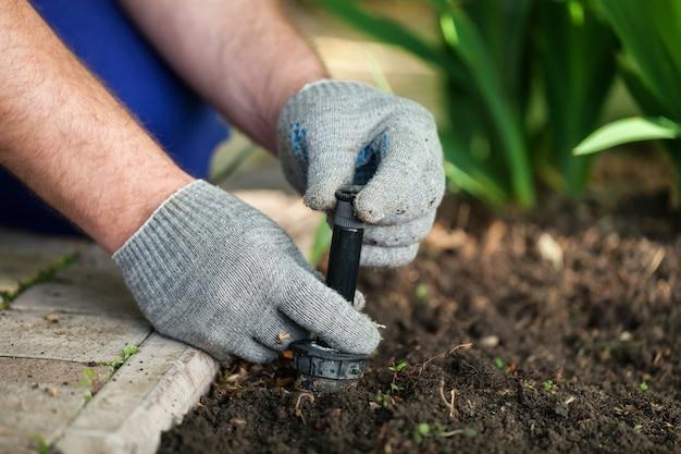 Installazione di irrigatori per campi in erba da parte di un installatore professionale di sistemi di giardinaggio caucasici.