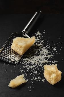 Primo piano del formaggio grattugiato su un tavolo da cucina scuro. bocconcini di parmigiano sul tavolo della cucina