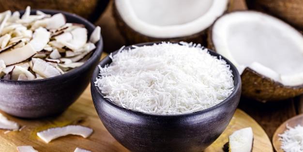 Cocco grattugiato all'interno di una ciotola di argilla, con pezzi di cocco e cocco sullo sfondo, ingrediente culinario per dolci