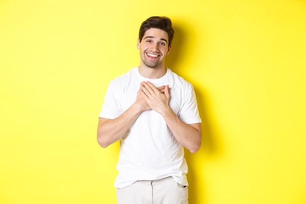 Grato bel ragazzo in maglietta bianca, tenendo le mani sul cuore e sorridendo compiaciuto, esprimere gratitudine, ringraziare per qualcosa, in piedi sopra il muro giallo
