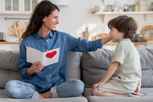 La mamma riconoscente tocca i capelli del figlio del bambino carino tenere la cartolina con i saluti per la festa della mamma siediti sul divano a casa