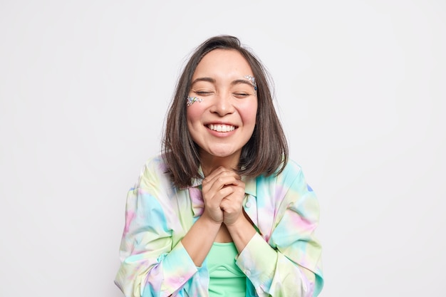 Grato positivo donna asiatica stringe le mani ha bellezza viso sorride a trentadue denti tiene gli occhi chiusi vestito con camicia colorata casual anticipa qualcosa di molto piacevole isolato sul muro bianco