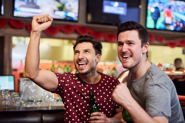 Appassionati di sport riconoscenti che guardano la partita sportiva