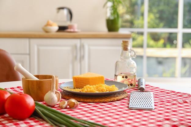 Grattugia e diversi prodotti sul tavolo della cucina