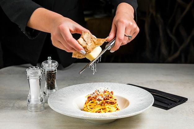 Grattugiare il parmigiano su un piatto di pasta alla carbonara