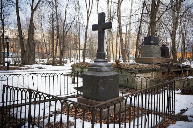 Tomba con croce nera nel cimitero innevato con alberi spogli, edifici residenziali in lontananza - cimitero luterano di smolenskoe, russia, san pietroburgo, marzo 2021