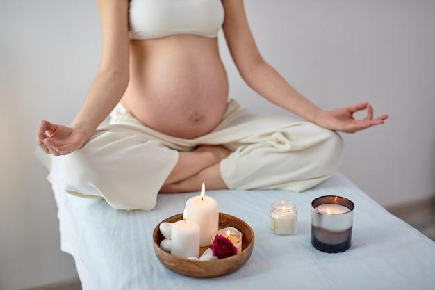 Gravida giovane femmina pratiche yoga in camera luminosa, salute durante la gravidanza. la futura mamma in abito casual, seduta con le gambe incrociate, meditando. maternità, gravidanza armoniosa. copia spazio