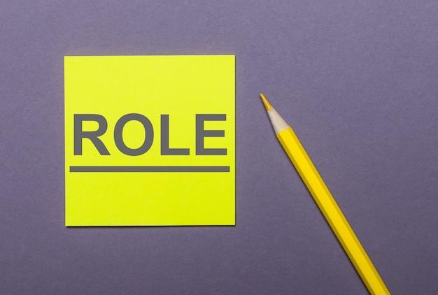 Su uno sfondo grigio, una matita gialla brillante e un adesivo giallo con la parola role