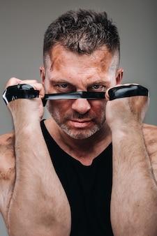 Su uno sfondo grigio c'è un uomo malconcio con una maglietta nera che sembra un combattente e si prepara a combattere.