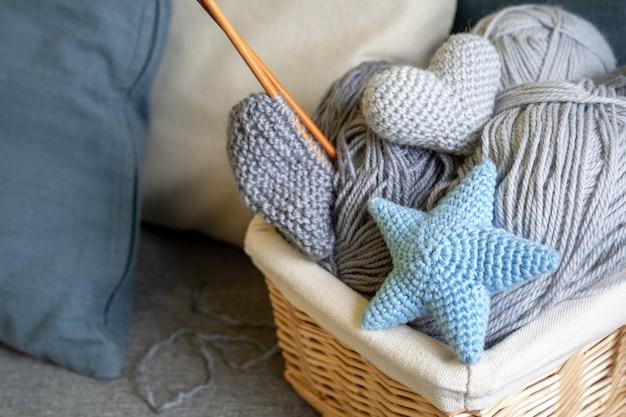 Gomitoli grigi di lana e ferri da maglia in un cesto di vimini stanno su un divano grigio con cuscini