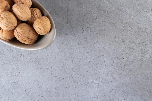 Ciotola grigia di noci sgusciate organiche su fondo di pietra.
