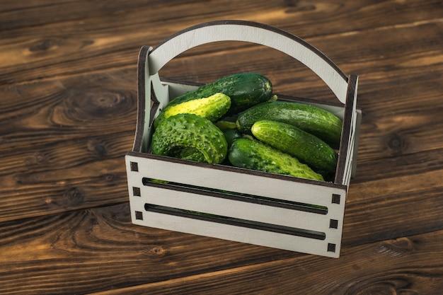 Una scatola grigia con cetrioli su un tavolo di legno.