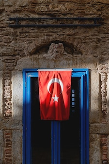 Un edificio grigio con bandiera turca sulla finestra blu alla luce del sole