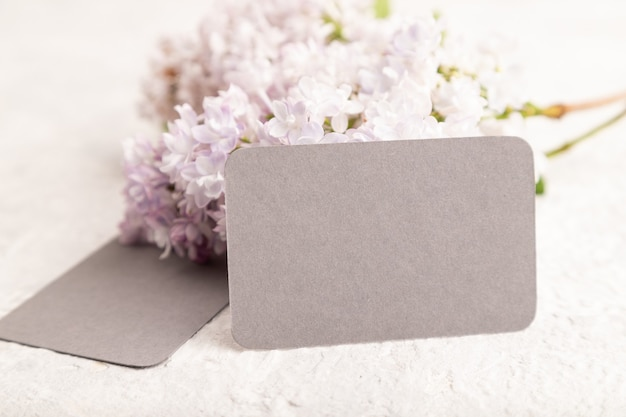Biglietto da visita grigio con fiori lilla su sfondo grigio cemento. vista laterale, copia spazio,