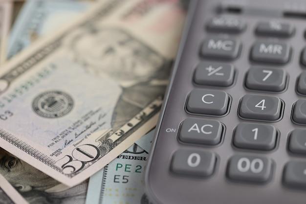 Calcolatrice grigia che si trova sul primo piano delle banconote in dollari. concetto di pagamento delle tasse annuali