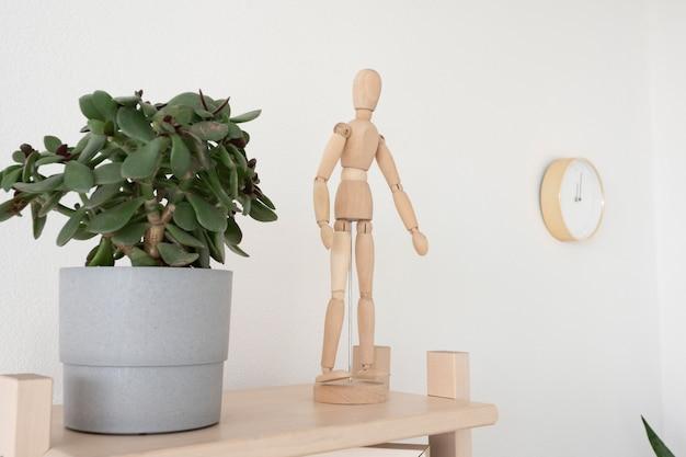Vaso in ceramica grigia con un fiore e una figura in legno di un uomo su una mensola in legno.