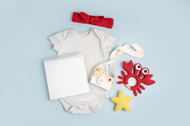 Simpatico body grigio per bebè con carta finta. set di vestiti e accessori per bambini. moda neonato. disposizione piatta, vista dall'alto