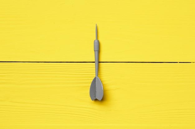Freccia grigia del dardo sulla vista superiore dello spazio della copia del fondo giallo