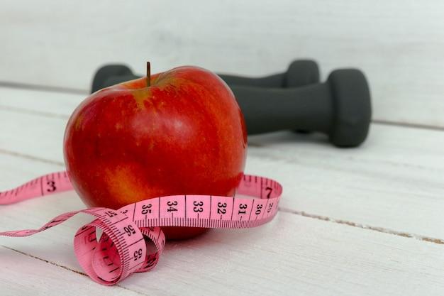 Manubri grigi, mela rossa e nastro di misurazione. mangiare sano e fitness. cibo sano e sport.