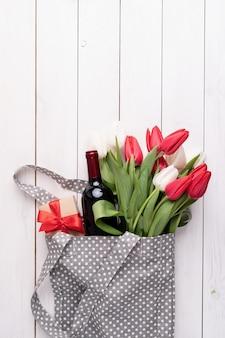 Borsa di stoffa grigia piena di tulipani colorati e bottiglia di vino
